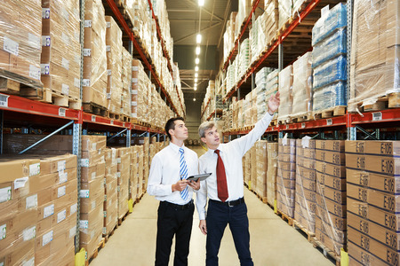 warehouse equipment: two managers workers in warehouse with bar code scanner