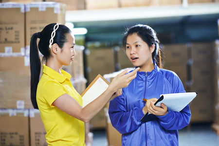 warehousing: two young chinese female workers in uniform in discussing warehousing system