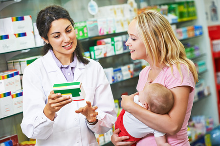 pharmacist chemist woman giving vitamins to mother with child in pharmacy drugstore