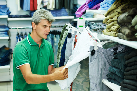 man choosing trousers during shopping at garments clothing shop photo