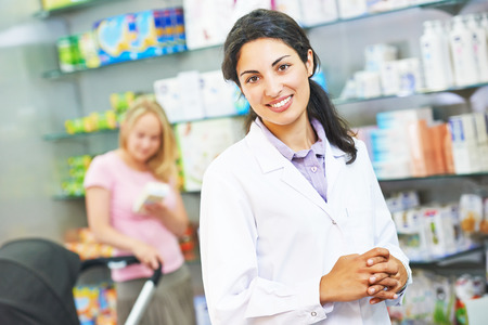portrait of cheerful female pharmacist chemist woman in pharmacy drugstore