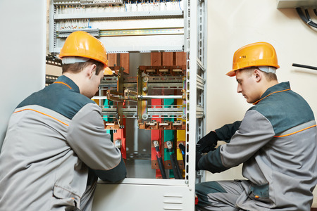 electrician builder engineer workers with electric cable wiring of fuse switch box photo