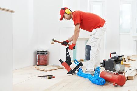 carpenter worker installing wood floor parquet board during flooring work with hammer photo