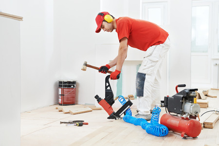 tongue and groove: carpenter worker installing wood floor parquet board during flooring work with hammer