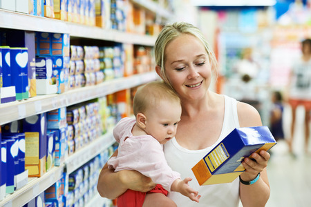 woman choosing children food with little baby child girl on hands during supermarket shopping Stock Photo