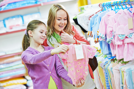 pregnant woman and little girl choosing newborn baby clothes during shopping at garments supermarket Фото со стока