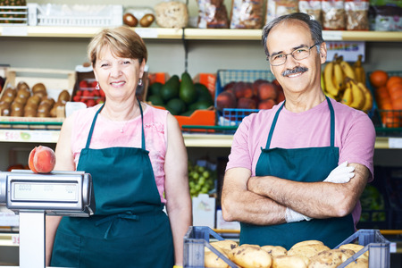 retailer: adult senior sale man with female assistant in fruit vegetable market shopping store Stock Photo