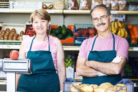 tiendas de comida: hombre adulto venta senior con asistente femenina en la fruta tienda de compras en el mercado de verduras