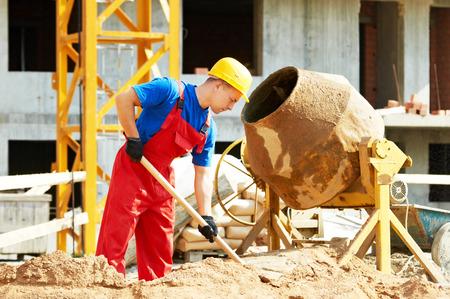 mortero: hombre constructor trabaja con la pala durante la preparación del mortero de cemento solución concreta en el mezclador en el sitio de construcción