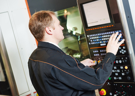 milling machine: industrial worker programming cnc turning machine center for metal working at manufacture workshop Stock Photo
