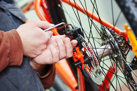 Mechanic serviceman repairman installing assembling or adjusting bicycle gear on wheel in workshop Stock Photo