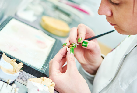 prosthodontics: Dental technician painting tooth during work on dentures at prosthesis laboratory Stock Photo