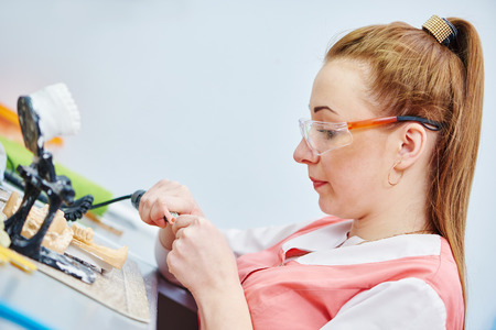 prosthodontics: Female dental technician working with tooth dentures at prosthesis laboratory