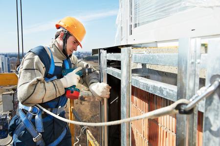 tile cladding: worker builder make ventilation facade construction on a high building