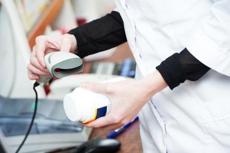 bar codes: pharmaceutical female worker scanning barcode of medicine drug in a pharmacy drugstore