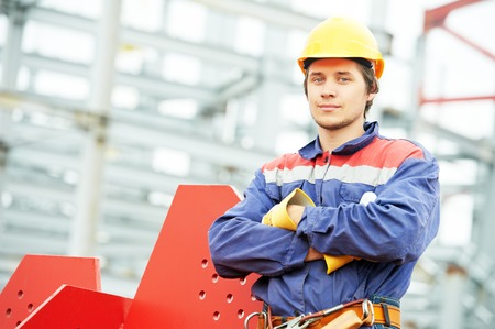 builder worker in uniform and safety protective equipment at construction site in front of metal construction frames Stock Photo