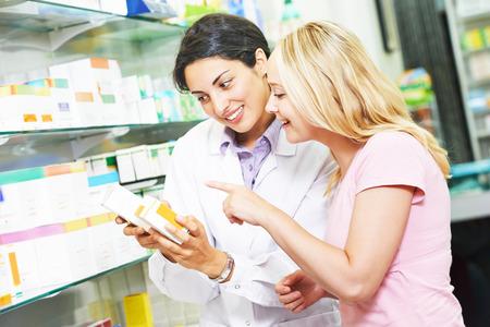apothekerchemicus vrouw helpt om medicijnen te kiezen voor jonge vrouwelijke koper in de farmacie drogisterij Stockfoto