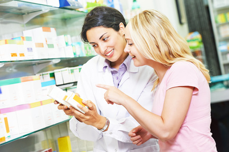 pharmacist chemist woman helps to choose medicine for young to female buyer in pharmacy drugstore
