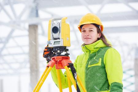 teodolito: trabajador agrimensor sexo femenino que trabaja con equipos de tránsito teodolito en la construcción de obra de construcción al aire libre Foto de archivo
