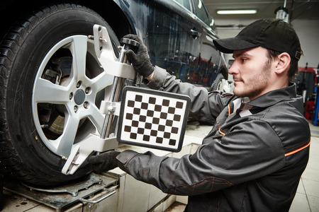 machine: car mechanic installing sensor during suspension adjustment and automobile wheel alignment work at repair service station