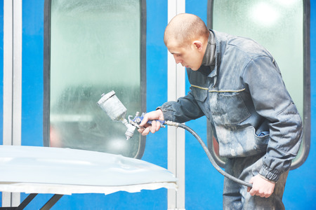 priming: auto mechanic worker priming a car bonnet before painting in a chamber during repair work Stock Photo