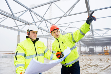 high visibility: engineers construction foreman managers outdoors indoors at building site with blueprints