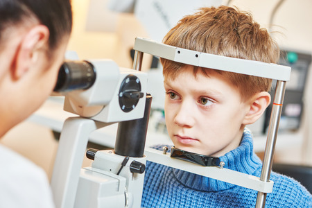 doctor of optometry: Child optometry. female optometrist optician doctor examines eyesight of little boy patient in eye ophthalmological clinic