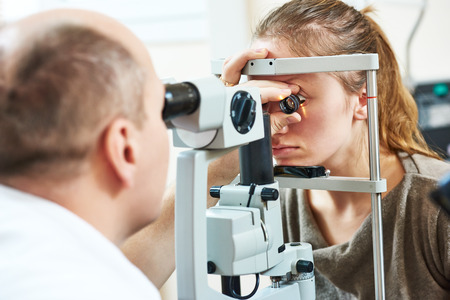 doctor of optometry: Adult optometry. male optometrist optician doctor examines eyesight of young woman patient in eye ophthalmological clinic