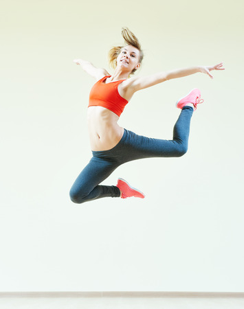 dancing club: fitness instructor jumping during aerobics dancing exercises in sport club