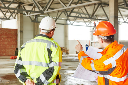 male engineers construction foreman managers outdoors at building site with blueprints Standard-Bild