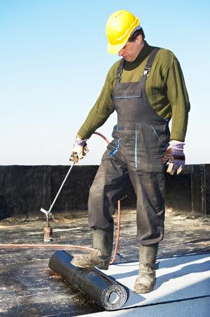 Dachdecker Vorbereitung Teil Bitumendachpappe Rolle für das Schmelzen von Gas-Heizung Brennerflamme