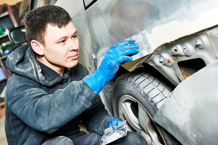auto mechanic worker plastering body car at automobile repair and renew service station shop before painting restoration photo