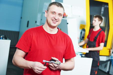 milling center: lavoratore industriale meccanica a CNC centro fresatrice in strumento di laboratorio produzione