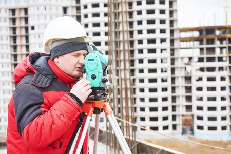 teodolito: topógrafo trabaja con equipos de tránsito teodolito en el sitio de construcción