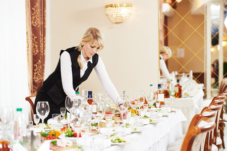 banquet table: Restaurant catering services. waitress serving banquet table
