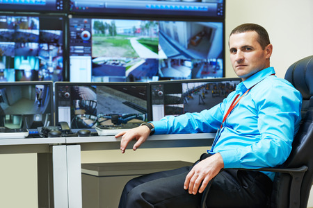 security monitoring: security guard watching video monitoring surveillance security system Stock Photo