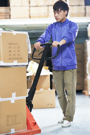 stacker: Male chinese worker with fork pallet truck stacker in warehouse loading group of boxes packages