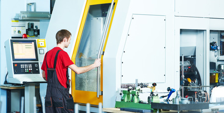 fettler: mechanical industrial worker at cnc milling machine center in tool manufacture workshop