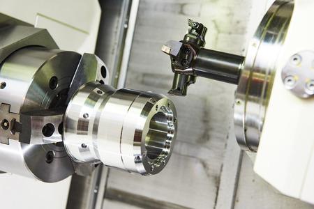 metalworking  industry: multi cutting tool pefroming facing cut of metal detail on lathe machine in workshop