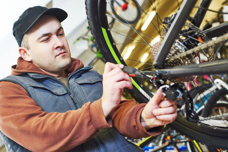 mountain bicycling: Mechanic serviceman repairman installing assembling or adjusting bicycle gear on wheel in workshop Stock Photo