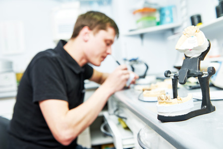Dental technician working with tooth dentures at prosthesis laboratory