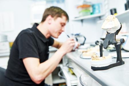 laboratorio dental: Técnico dental que trabaja con el diente dentaduras en el laboratorio de prótesis Foto de archivo