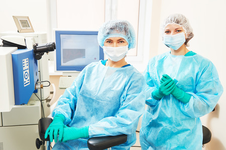 laser surgery: Female surgeon and assistant nurse portraits in uniform in eye vision surgery operation room at medical clinic Stock Photo