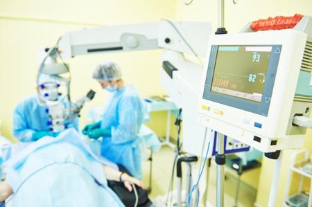 cirujano: equipo de cirujano en uniforme frente a cirug�a de la visi�n del ojo sala de operaci�n en la cl�nica m�dica