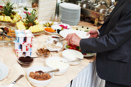 Hotel restaurant catering service. Man with food at morning buffet style smorgasbord breakfast photo