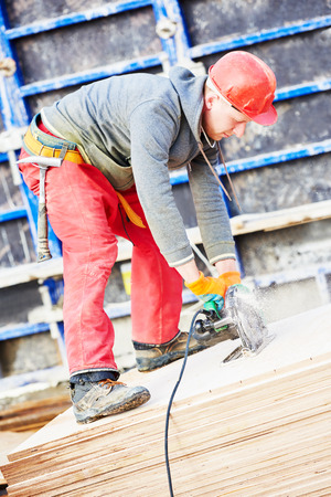 concreting: builder carpenter worker with disk saw cutting plywood for falsework construction before concreting at building site Stock Photo