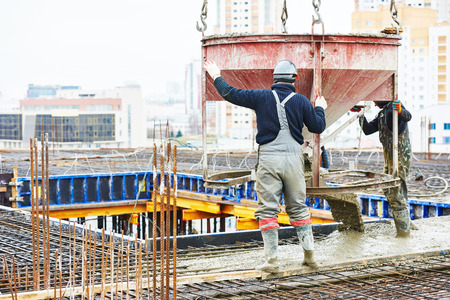 concreting work: construction site worker during concrete pouring into formwork at building area with skip