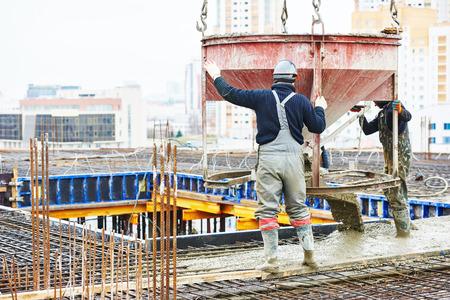 travaux de bétonnage: chantier de construction travailleur pendant le coulage du béton dans un coffrage à l'aire de bâtiment avec saut Banque d'images