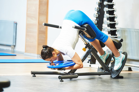 Hyperextension. fitness and sport concept. personal coach trainer woman work out at a gym with heavy weight photo