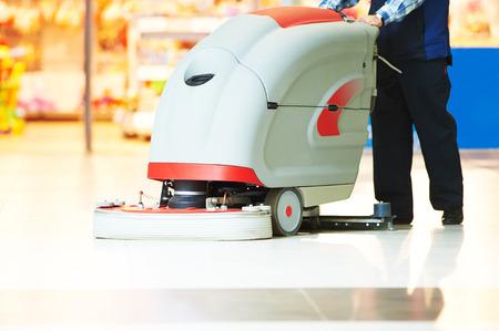 La cura dei pavimenti e la pulizia servizi con lavatrice in negozio negozio supermercato Archivio Fotografico - 40274073